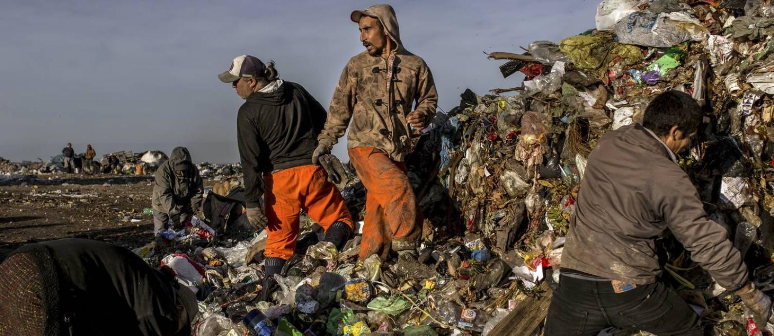 Um grupo de pessoas revolve um lixão na cidade de Paraná, na Argentina, buscando comida, roupas e material reciclável para vender Foto: SARAH PABST / NYT