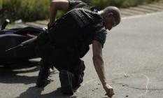 Policial analisa cena de crime em São João de Meriti, na Baixada Fluminense Foto: Gabriel de Paiva / Agência O Globo (05/04/2019)