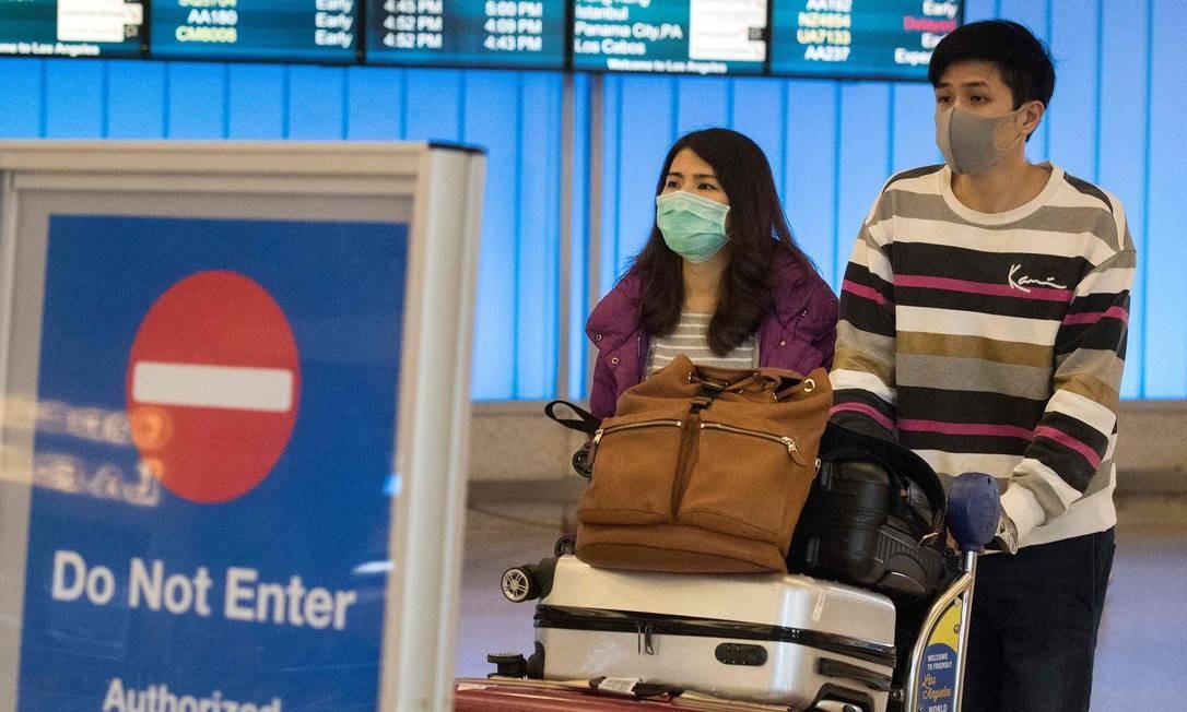 Passageiros usam máscaras de proteção ao chegarem no aeroporto internacional de Los Angeles, na Califórnia. Foto: MARK RALSTON / AFP