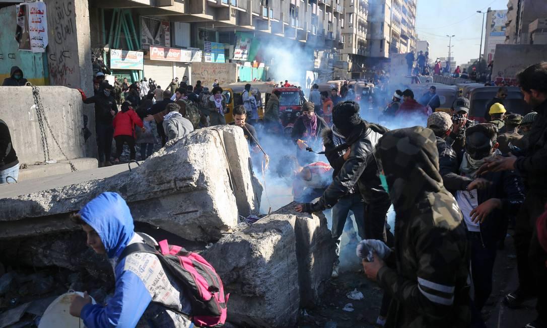 Manifestantes tentam evitar as bombas de gás lançadas pelas forças de segurança do Iraque em Bagdá. Polícia usou armas de fogo para reprimir os manifestantes Foto: AHMAD AL-RUBAYE / AFP