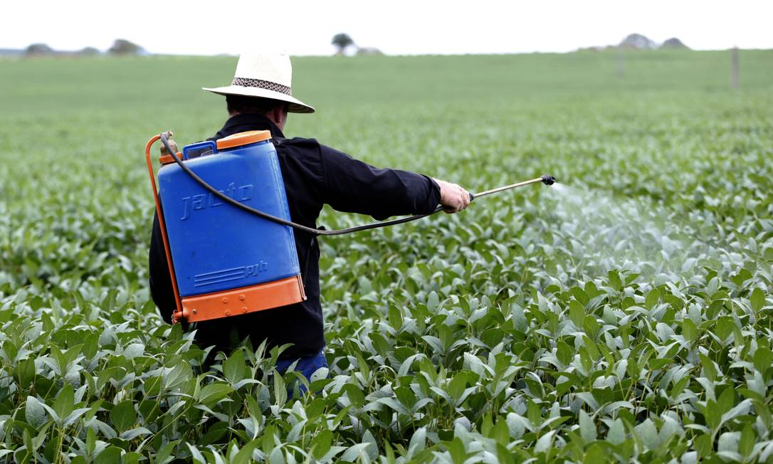 Agricultor aplica agrotóxico em plantação de soja, sem uso de equipamento de proteção; governo liberou mais 42 produtos hoje Foto: Michel Filho/26-1-17 / Agência O Globo