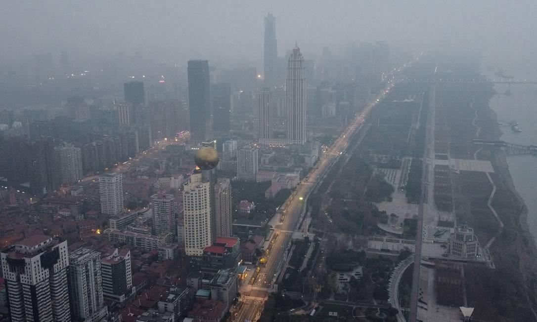 Vista aérea de regiões residenciais e comerciais na cidade de Wuhan, na China, considerada o epicentro da crise do coronavírus. Ruas vazias refletem quarentena imposta pelo governo Foto: HECTOR RETAMAL / AFP