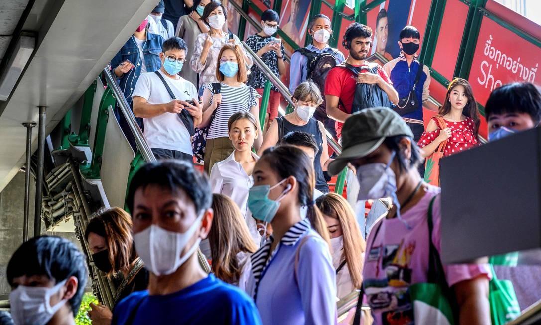 Pessoas com máscaras chegam à estação de trem BTS Sky, em Bangcoc, na Tailândia. País detectou oito casos de coronavírus até esta segunda-feira (27). Foto: MLADEN ANTONOV / AFP