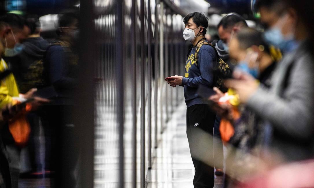 Passageiros com máscaras esperam trem em uma plataforma do metrô durante feriado público do Ano Novo Lunar do Rato, em Hong Kong Foto: ANTHONY WALLACE / AFP