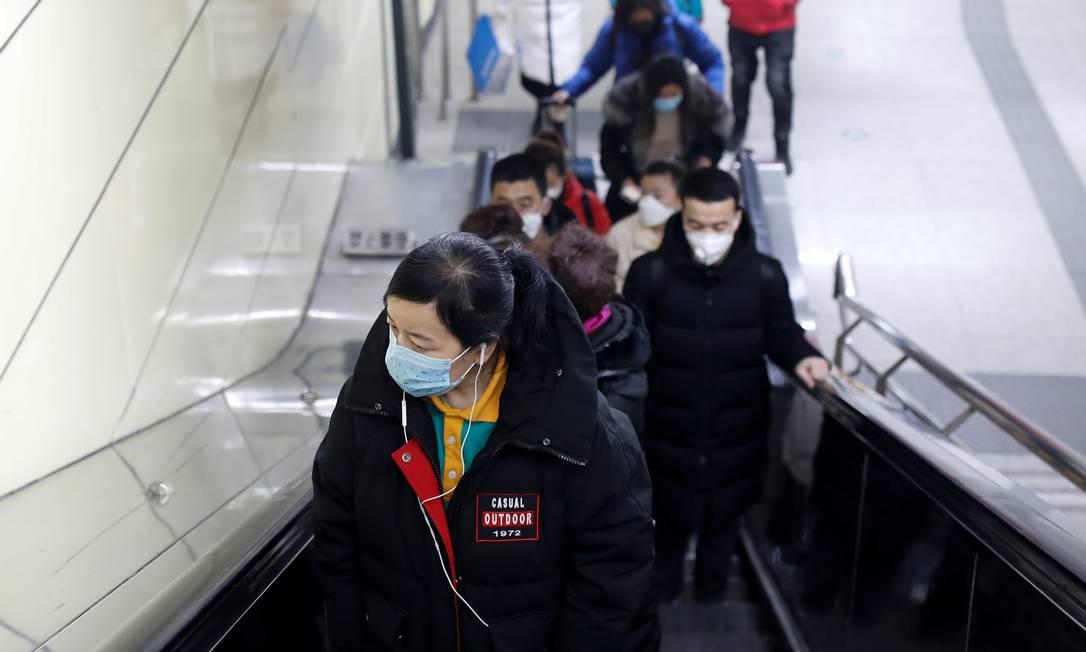 Pessoas usam máscaras de proteção na escada da estação de metrô de Pequim, na China. Foto: CARLOS GARCIA RAWLINS / REUTERS