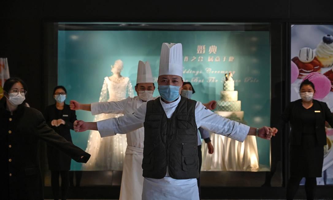 Funcionários usando máscaras protetoras exercitam-se no saguão de um hotel em Wuhan, na província central de Hubei, na China Foto: Hector Retamal / AFP