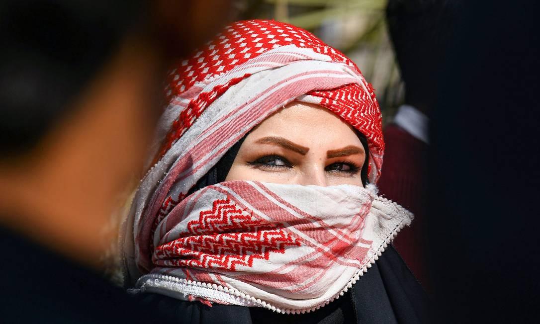 Estudante com rosto coberto com lenço é vista durante manifestação antigovernamental na cidade de Najaf, no santuário central do Iraque Foto: Haidar Hamdani / AFP