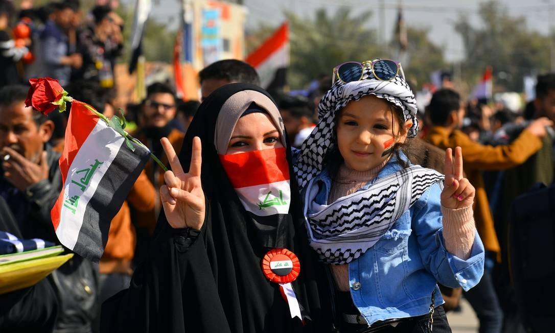 Mãe posa com a filha enquanto faz sinal de V com as mãos, em protesto em Najaf Foto: Haidar Hamdani / AFP