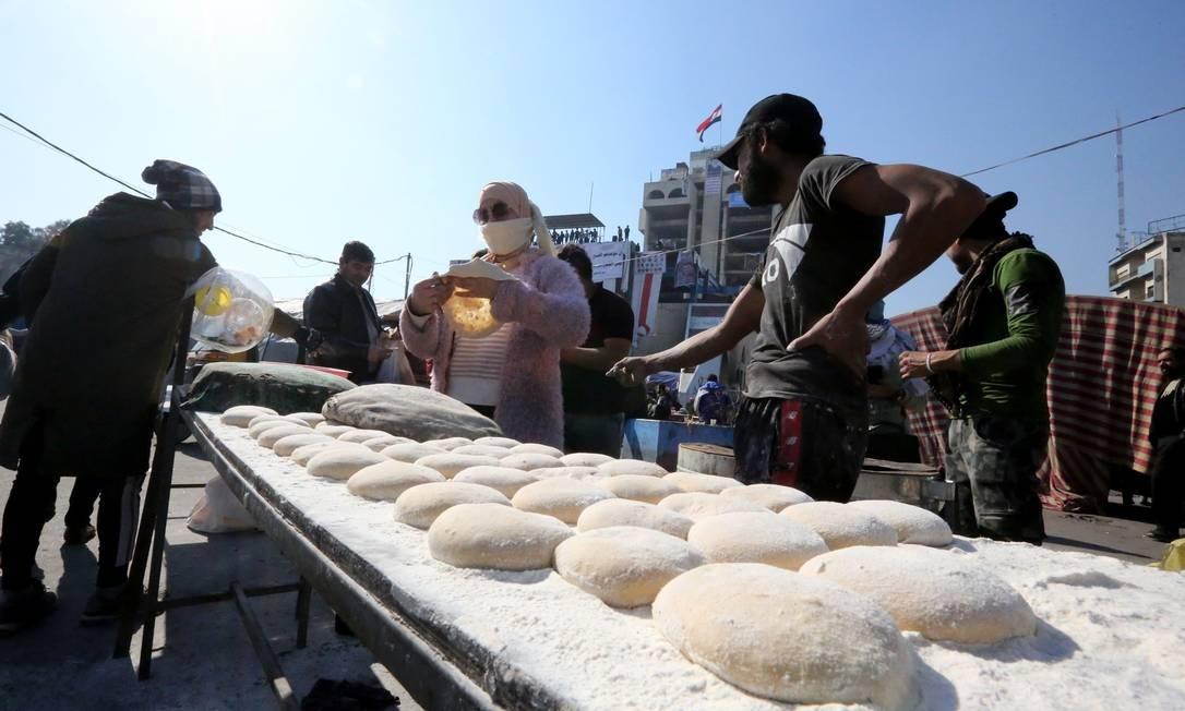 Apoiadores assam pão fresco ao ar livre enquanto manifestações acontecem na praça Tahrir, no centro de Bagdá, nesta terça-feira Foto: Sabah Arar / AFP
