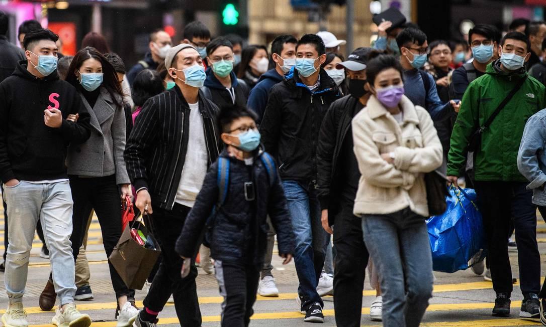Pedestres caminham em rua de Hong Kong durante o feraido do Ano Novo Lunar com máscaras contra coronavírus Foto: ANTHONY WALLACE / AFP