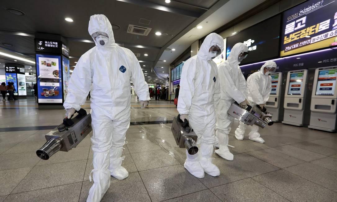 Trabalhadores desinfetam terminal de ônibus em Gwangju, na Coreia do Sul, um dos 14 países atingidos pelo coronavírus originário de Wahun, na China Foto: - / AFP