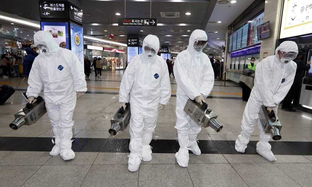 Funcionários de saúde com roupas protetoras desinfetam aeroporto na Coreia do Sul por temor do coronavírus Foto: - / AFP