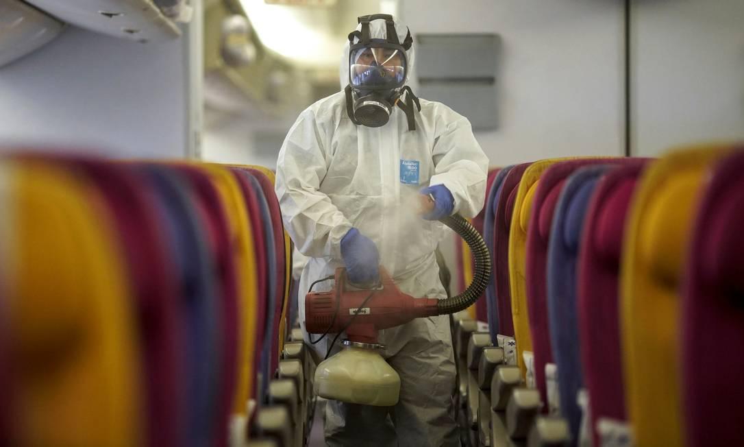 Homem desinfecta avião da cia Thai Airways contra o coronavírus Foto: ATHIT PERAWONGMETHA / REUTERS