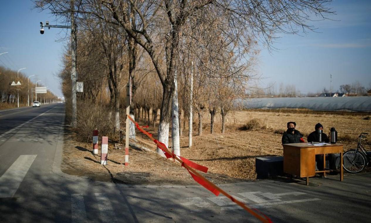 Membros de uma comunidade nos arredores de Pequim vigiam a entrada de uma para impedir a entrada de estrangeiros Foto: Carlos Garcia Rawlins / Reuters