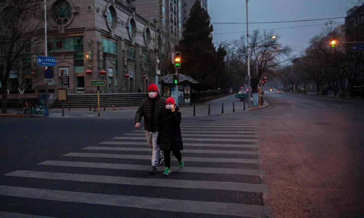 Um casal usando máscaras para impedir a propagação de um vírus mortal que começou em Wuhan, caminha em uma estrada vazia de Pequim Foto: Nicolas Asfouri / AFP