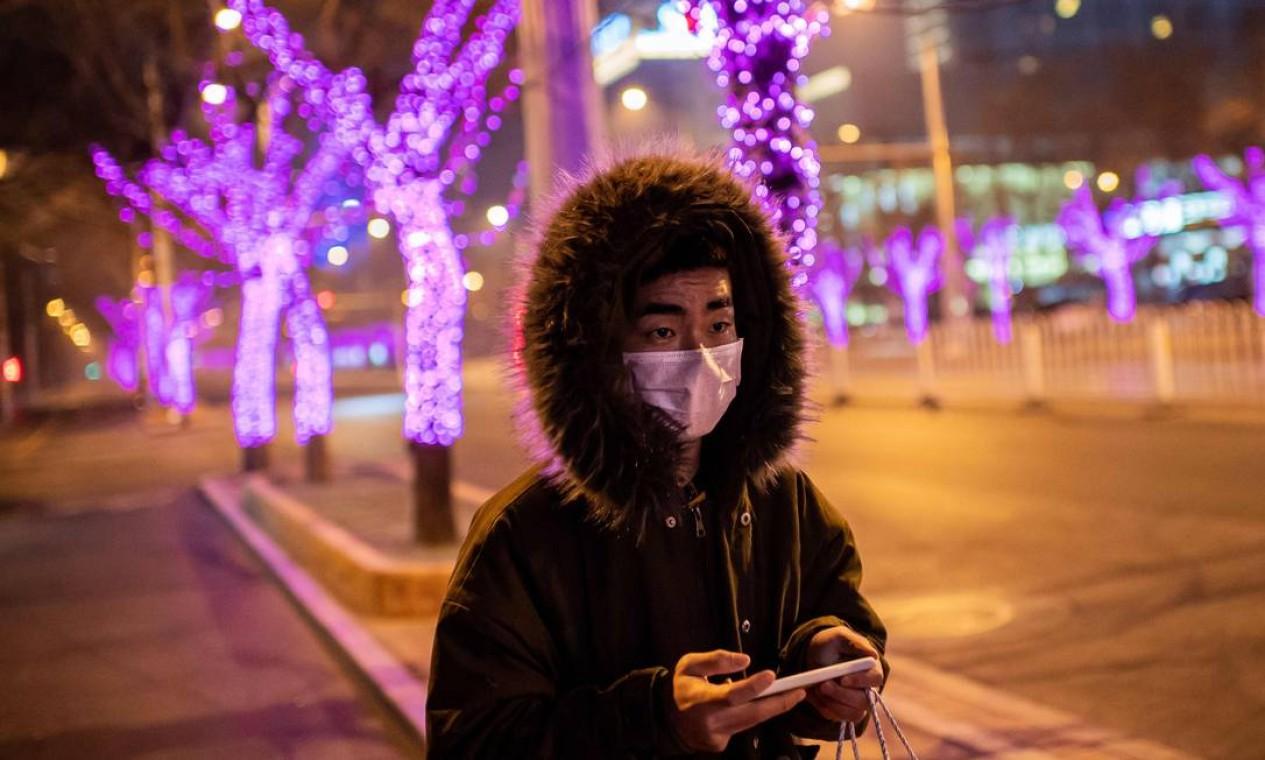 Um homem caminha solitariamente, em avenida que estaria movimentada antes do surto do novo coronavírus Foto: Nicolas Asfouri / AFP