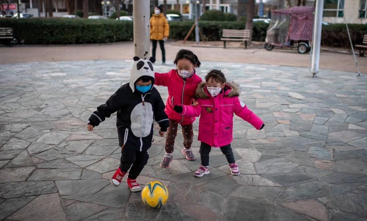 Crianças brincam usando máscaras protetoras para dentro de condomínio, em Pequim Foto: Nicolas Asfouri / AFP