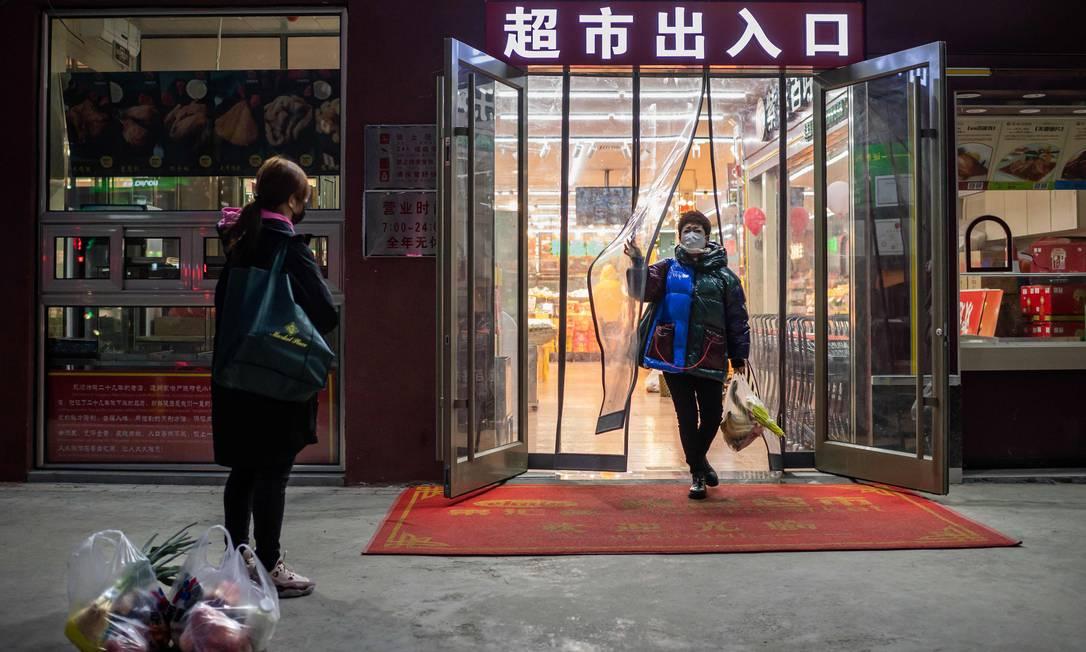 Usando máscaras cirúrgicas, amigas deixam supermercado em Pequim; capital da China viu movimento nas ruas e comércio despencar desde o início da crise do novo coronavírus, que já infectou mais de 6 mil pessoas no país Foto: NICOLAS ASFOURI / AFP