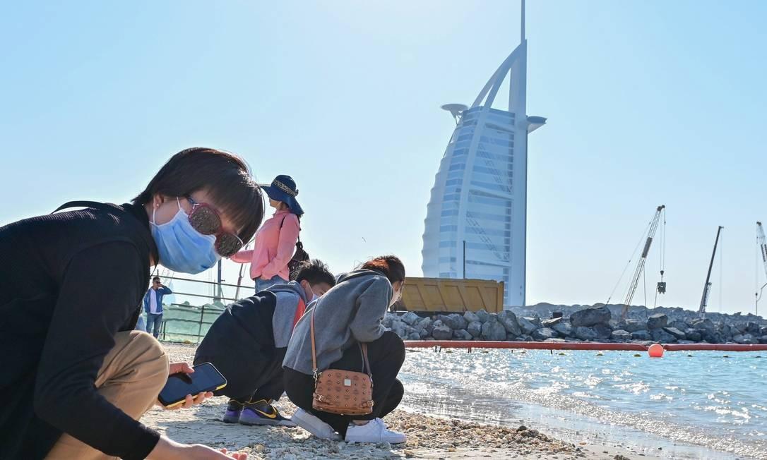 Turistas usam máscaras cirúrgicas em praia dos Emirados Árabes, que confirmaram os primeiros casos no Oriente Médio. Foto: GIUSEPPE CACACE / AFP