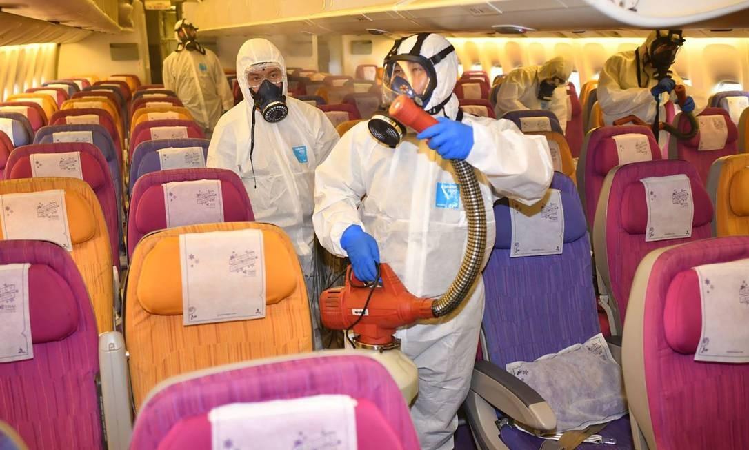 Funcionários da companhia aérea tailandesa Thai Airways desinfetam aeronave no hangar da empresa no aeroporto de Bangcoc, na tentativa de prevenir a disseminação do novo coronavírus Foto: HANDOUT / AFP