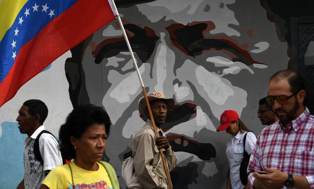 Homem segura bandeira venezuelana ao lado de mural com o rosto do falecido presidente Hugo Chávez, em Caracas Foto: YURI CORTEZ / AFP/14-01-2020