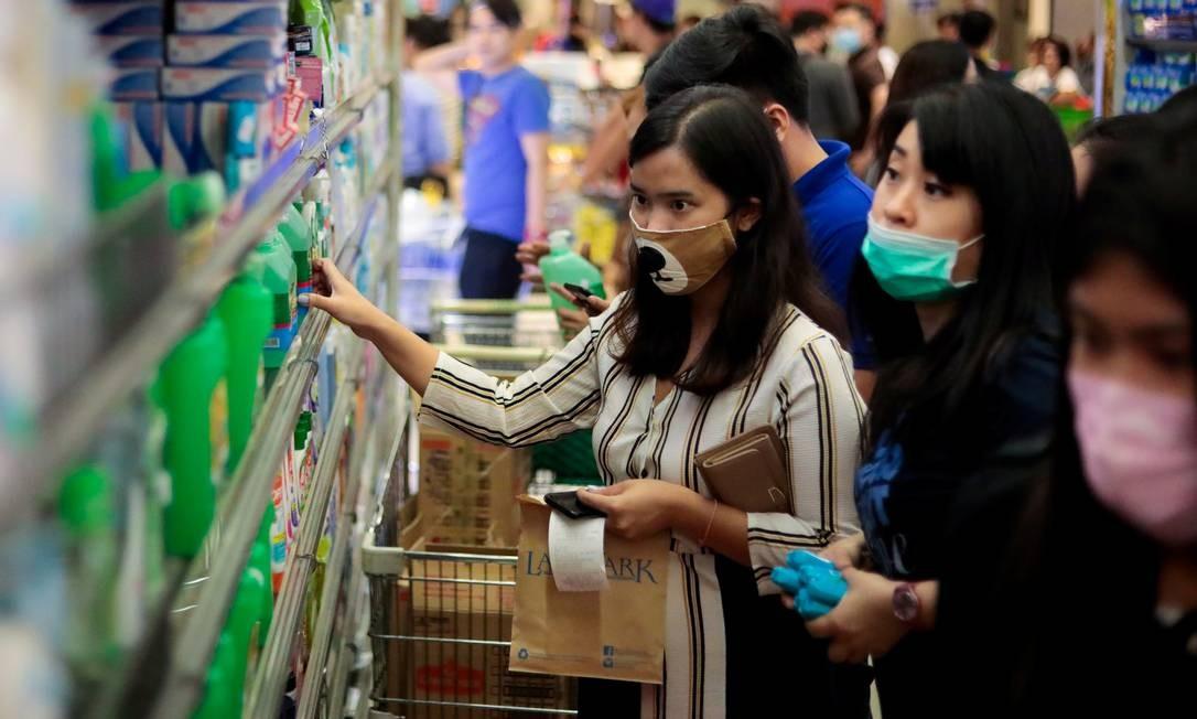 Pessoas armazenam garrafas de álcool depois que o governo filipino confirmou o primeiro caso do novo coronavírus no país, na cidade de Makati, Região Metropolitana de Manila Foto: ELOISA LOPEZ / REUTERS
