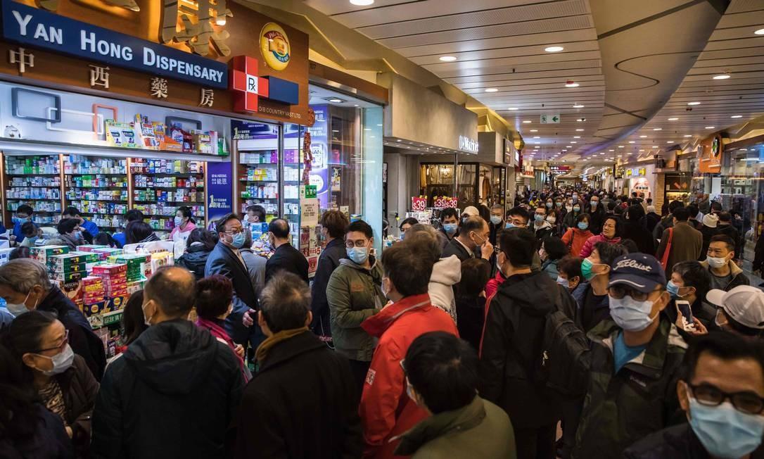 Pessoas esperam em fila do lado de fora de uma farmácia para comprar máscaras em Hong Kong Foto: DALE DE LA REY / AFP
