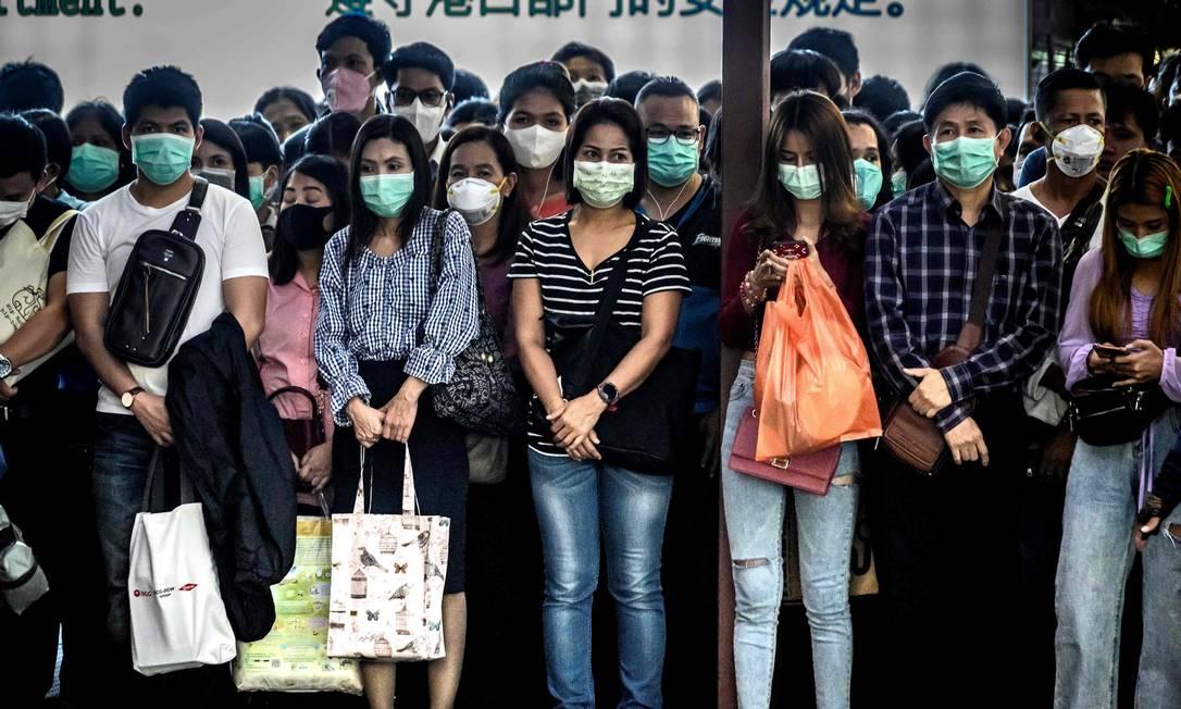 Passageiros de máscara esperam por barco em Bangkok, Tailândia Foto: MLADEN ANTONOV / AFP