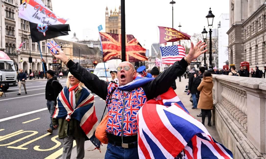 Apoiador do Brexit carrega bandeiras comemora divórcio nas ruas do Reino Unido Foto: GLYN KIRK / AFP