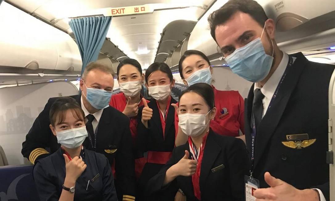 O comandante brasileiro Fabio D'Andrea (à esquerda) e a tripulação da Air Macau: máscaras passaram a ser itens indispensáveis nos voos Foto: . / Arquivo pessoal