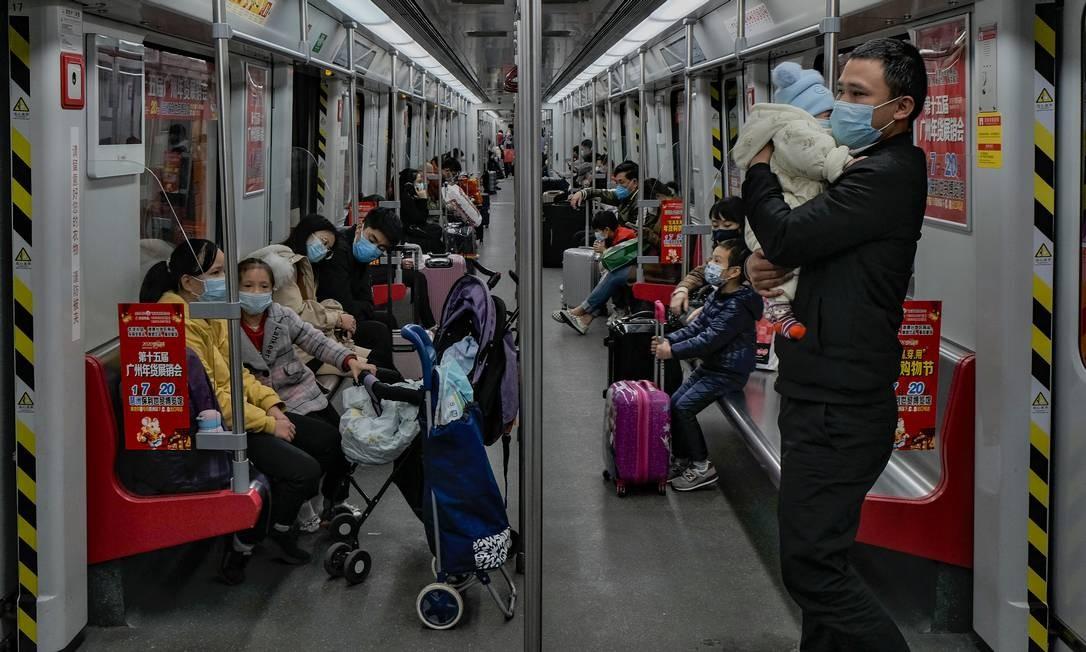 Homem tenta acalmar o filho, ambos usando máscaras de proteção, no metrô da cidade de Cantão, na China Continental Foto: Diego Herculano / Agência O Globo