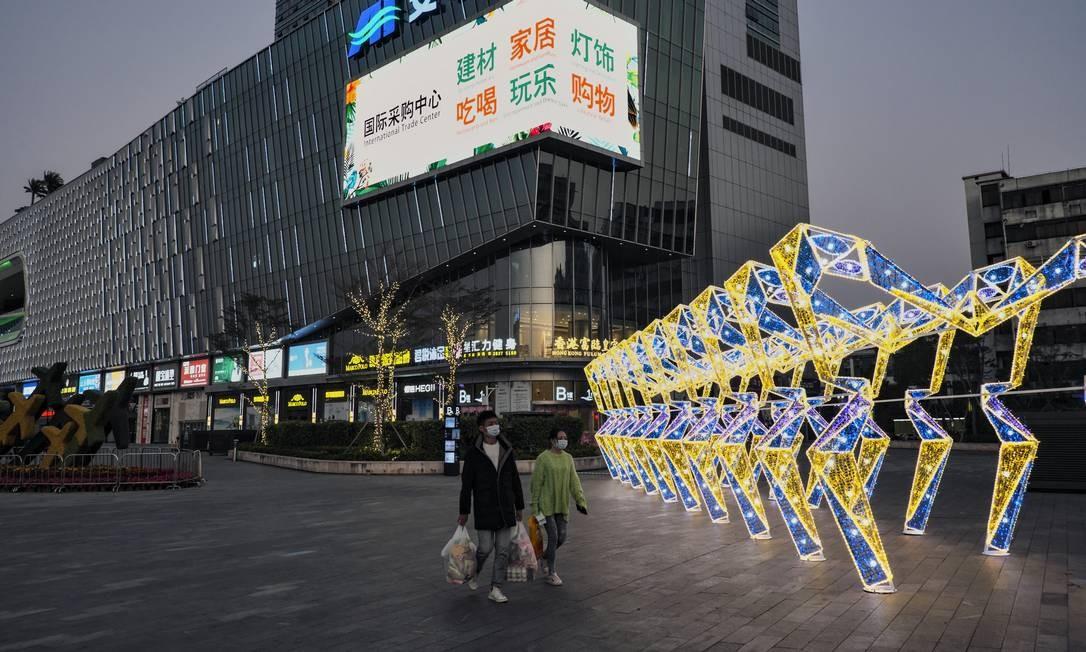 Casal de chineses carrega bolsas de supermercado próximo a um shopping bastante frequentado pelos chineses, mas que agora fica praticamente deserto devido à epidemia Foto: Diego Herculano / Agência O Globo