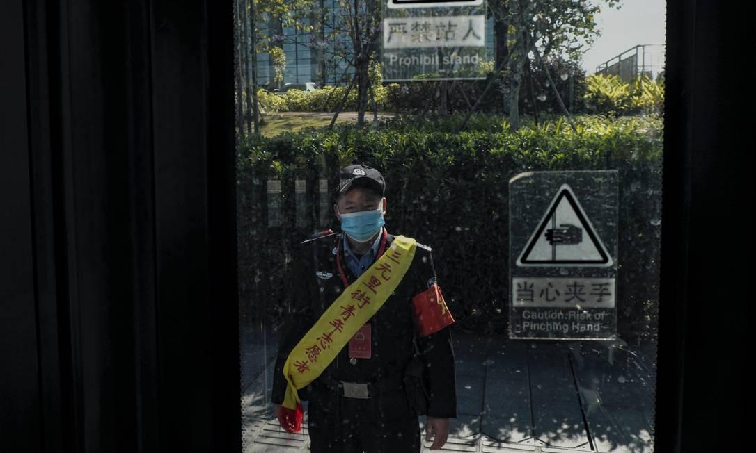 Um policial chinês é visto através da porta de um ônibus, durante uma blitz para conferir se todos os passageiros usavam máscaras Foto: Diego Herculano / Agência O Globo