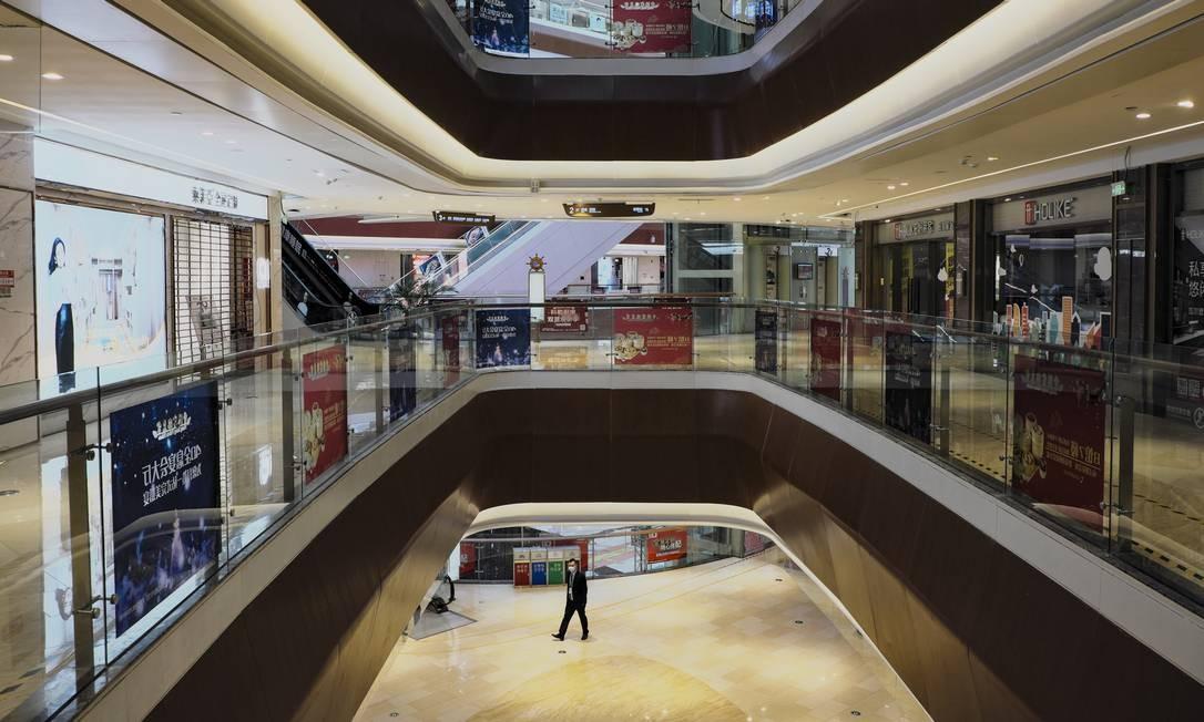 Um segurança caminha pelos corredores vazios de shopping em Cantão Foto: Diego Herculano / Agência O Globo