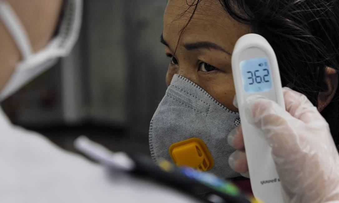 Uma mulher tem sua temperatura testada pelo segurança de uma estação do metrô. Guangzhou, China Continental, 25 de janeiro de 2020. Foto: Diego Herculano / Agência O Globo