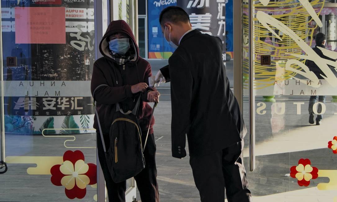 Um chinês com máscara de proteção tem a temperatura do corpo medida por um segurança de shopping Foto: Diego Herculano / Agência O Globo