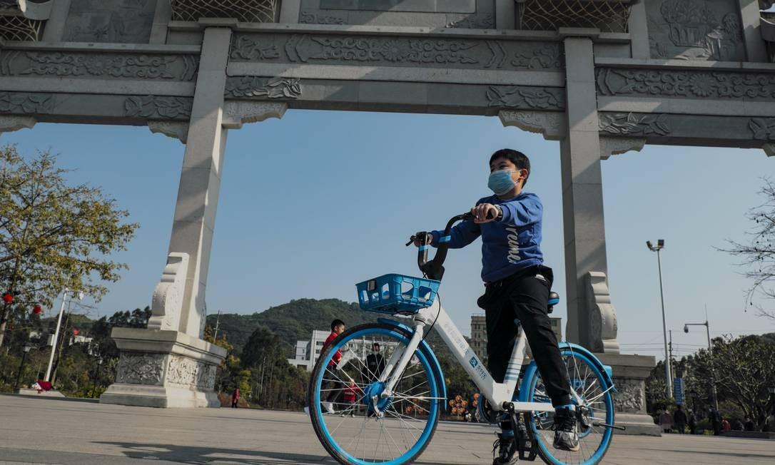 Criança chinesa usa máscara enquanto anda de bicicleta em parque na cidade de Cantão Foto: Diego Herculano / Agência O Globo