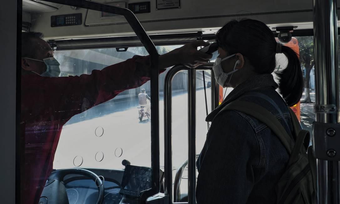 Uma passageira tem a temperatura do corpo medida pelo motorista de ônibus da cidade de Guangzhou, China Continental, 30 de janeiro de 2020. Foto: Diego Herculano / Agência O Globo