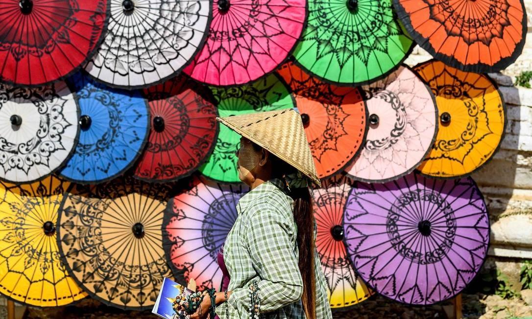 Suvenires, como os guarda-chuvas coloridos, são vendidos aos visitantes no complexo de templos de Mingun, que fica a cerca de 40 quilômetros de Mandalay, uma das maiores cidades de Mianmar Foto: Mladen Antonov / AFP