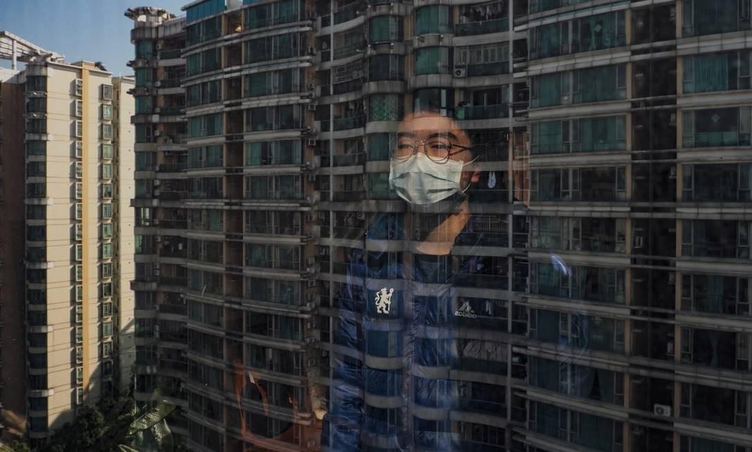 Liu Lixing, de 19 anos, estudante na Universidade de Estudos Estrangeiros de Cantão, olha pela janela de seu apartamento Foto: Diego Herculano / Agência O Globo