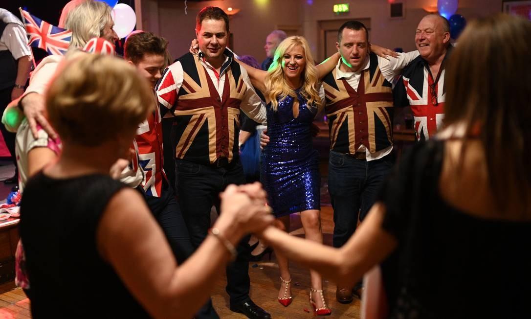 Apoiadores do Brexit dançam para comemorar a saída da UE, na noite de sexta, no Woolston Social Club, em Warrington, noroeste da Inglaterra Foto: OLI SCARFF / AFP/31-1-2020