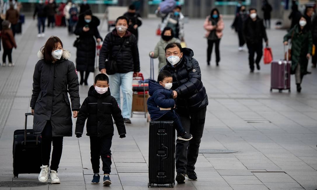 Os passageiros que usam máscaras faciais chegam de diferentes províncias à Estação Ferroviária de Pequim Foto: NOEL CELIS / AFP