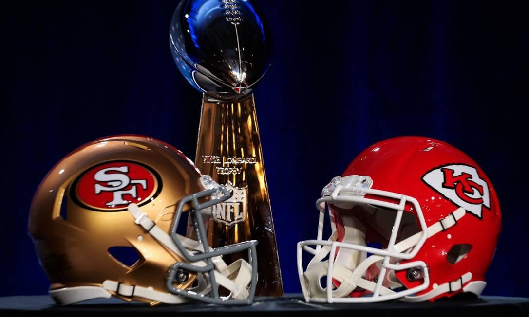 Troféu do Super Bowl, ao lado dos capacetes dos times que disputam a final: o São Francisco 49s e o Kansas City Chiefs Foto: Cliff Hawkins / AFP