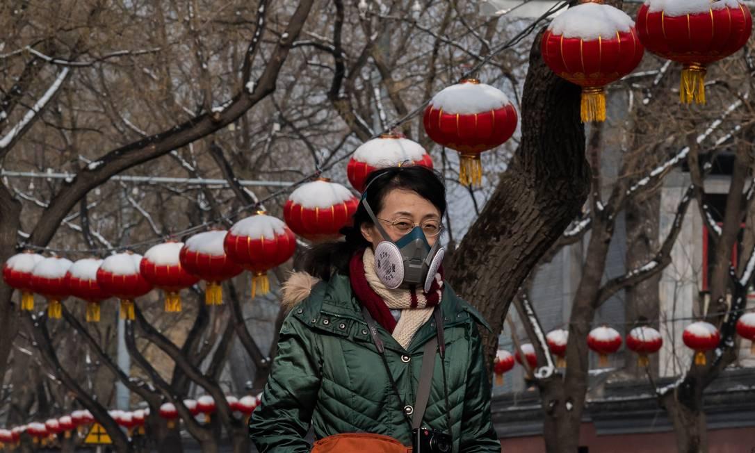 Uma mulher usando uma máscara protetora para impedir a propagação do vírus caminha em uma rua após uma nevasca em Pequim Foto: NICOLAS ASFOURI / AFP