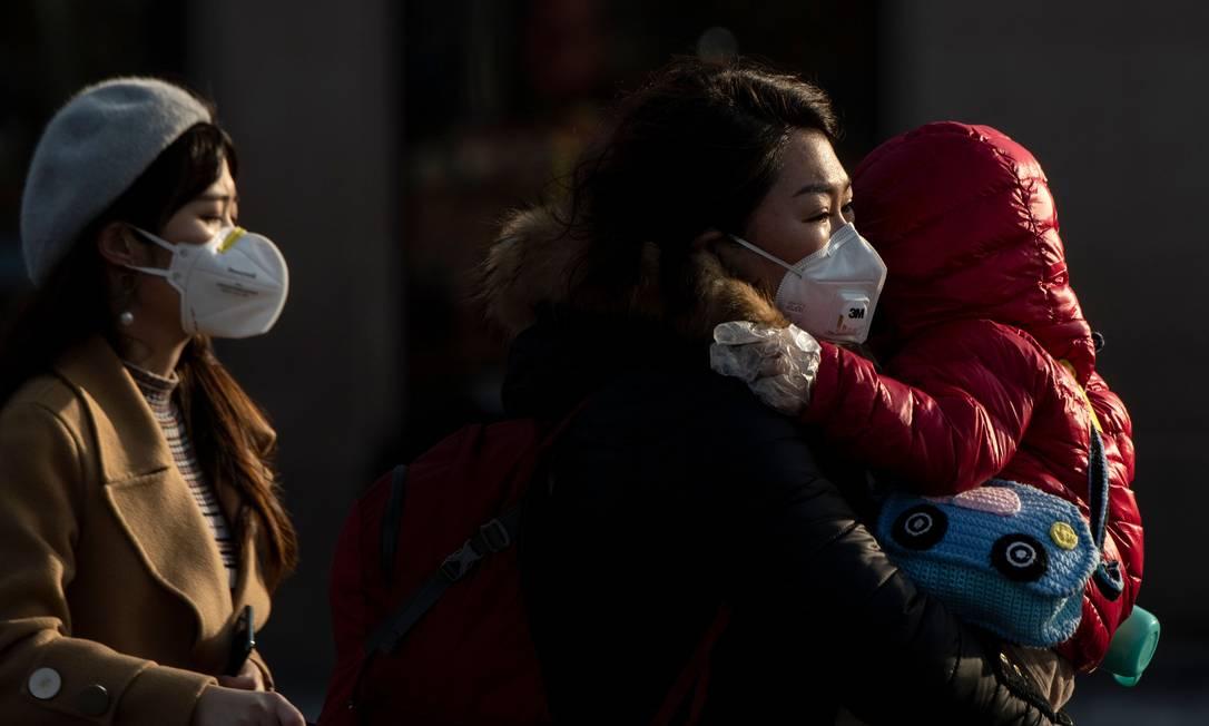 Turistas de máscara chegam à estação de trem de Pequim, na China. Foto: NOEL CELIS / AFP