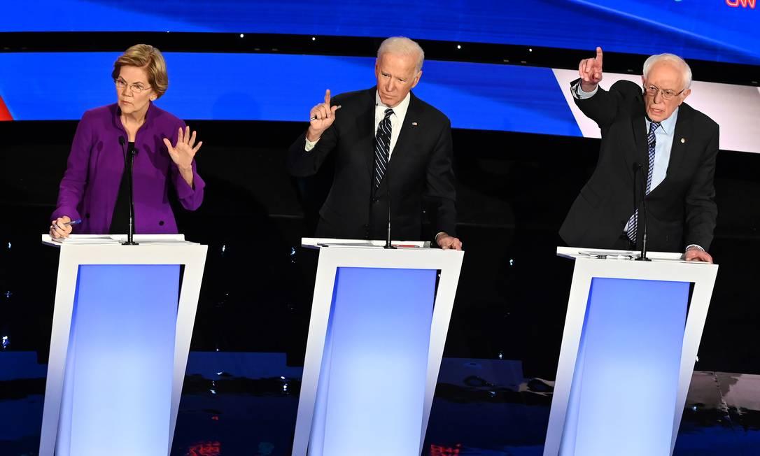 Senadores Elizabeth Warren e Bernie Sanders (D) e o ex-vice-presidente Joe Biden (C) participam de debate dos pré-candidatos do Partido Democrata à presidência, no dia 14 de janeiro Foto: ROBYN BECK / AFP