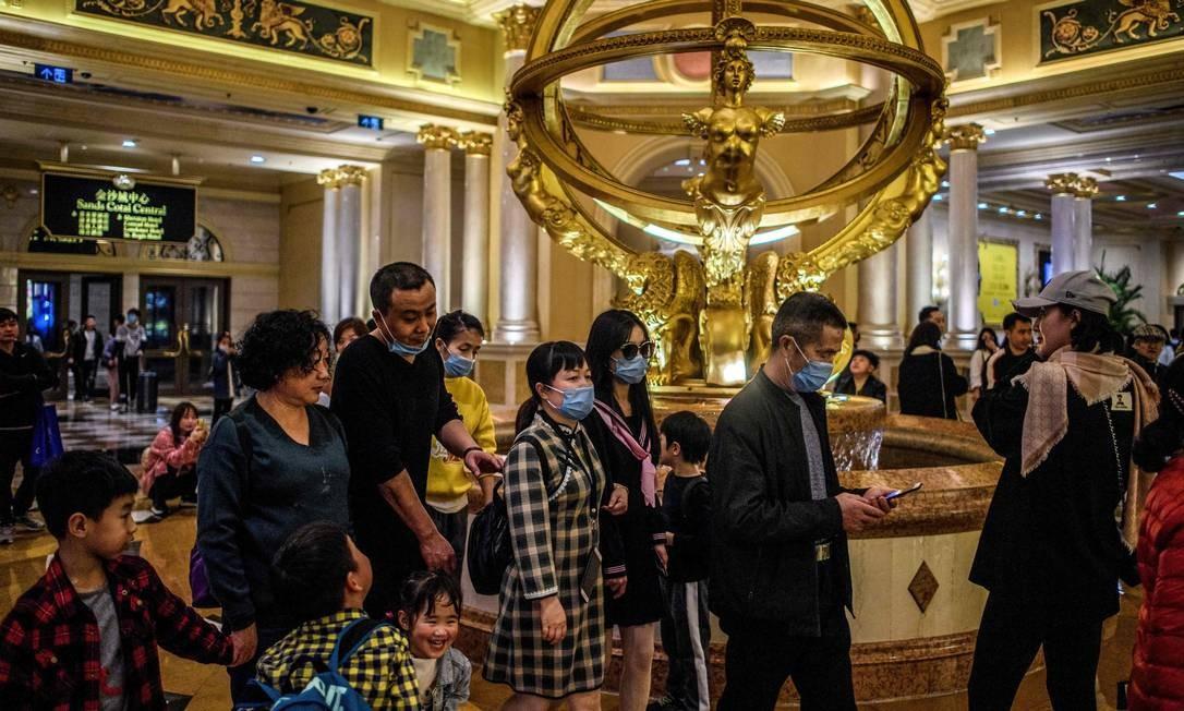 Foto feita em 22 de janeiro de 2020 mostra visitantes com máscaras faciais dentro do resort de cassino Venetian em Macau Foto: ANTHONY WALLACE / AFP