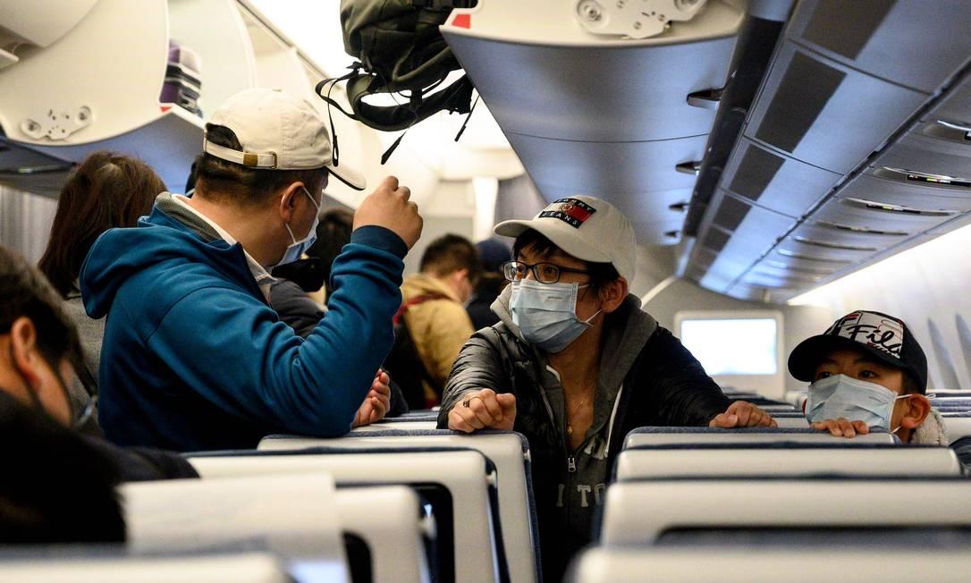 Passageiros usando máscaras aguardam para sair de avião no aeroporto internacional de Xangai Foto: NOEL CELIS / AFP