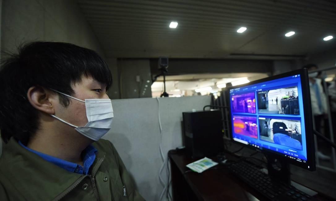 Funcionário monitora a temperatura corporal de passageiros que chegam na estação de trem em Hangzhou, China Foto: Barcroft Media / Barcroft Media via Getty Images