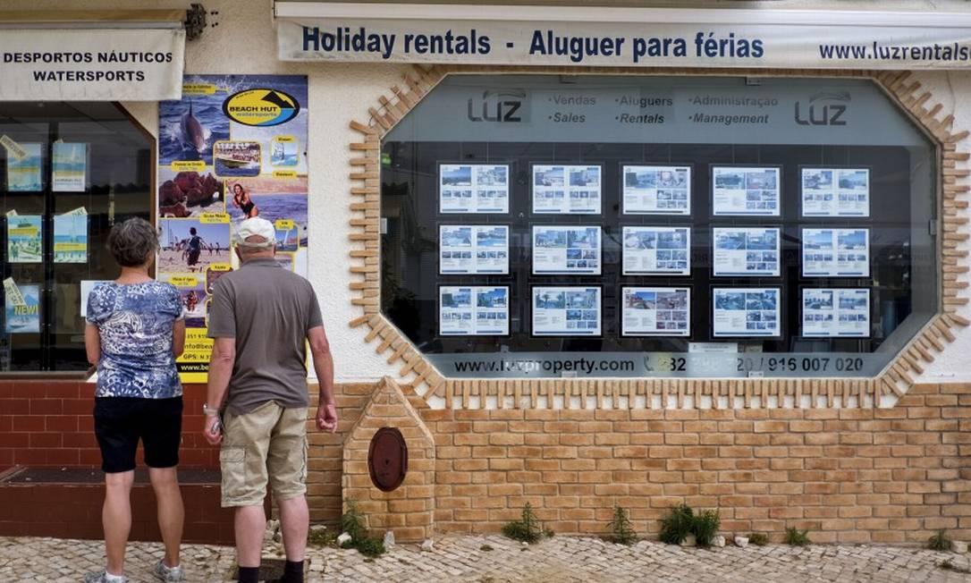 Foto mostra casal em frente à imobiliária na Praia da Luz, no Algarve Foto: Patricia de Melo Moreira / AFP / 28-04-2017